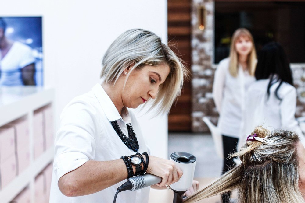 Mobile hairdresser working on ladies hair, drying with hairdryer